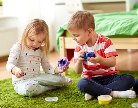 little kids with modelling clay or slimes at home
