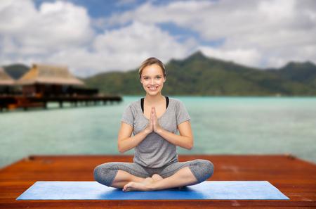 woman making yoga in and meditating lotus pose Foto de archivo