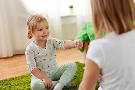 girls playing rock-paper-scissors game at home Standard-Bild - 99194814