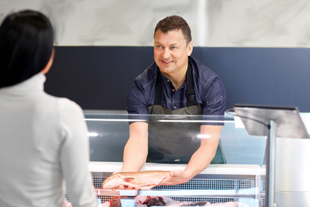 seller showing seafood to customer at fish shop Stock Photo