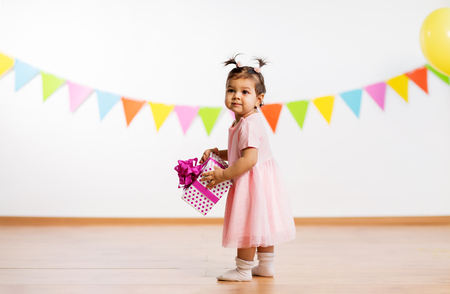 happy baby girl with gift box on birthday party