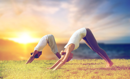 smiling couple making yoga dog pose outdoors