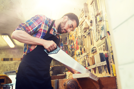 carpenter working with saw and wood at workshop