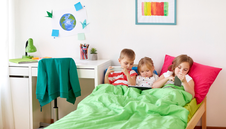 kids with tablet pc and smartphones in bed at home