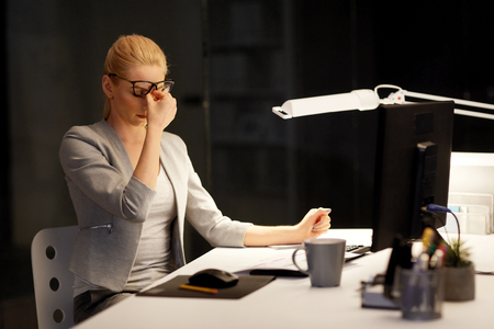 tired businesswoman working at night office