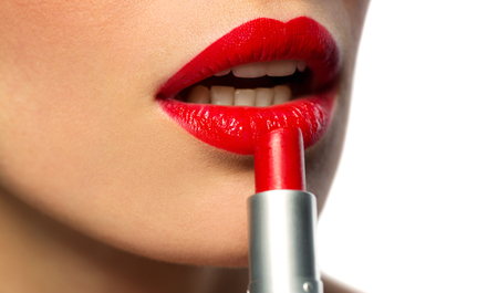 close up of woman applying red lipstick to lips Foto de archivo