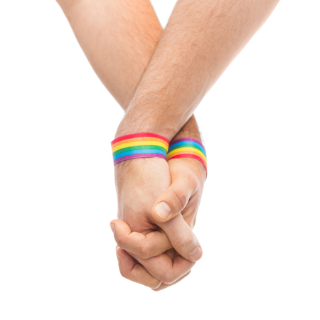 hands of couple with gay pride rainbow wristbands