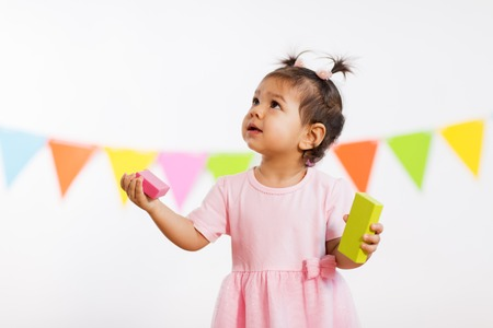 happy baby girl with toy blocks at birthday party