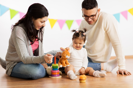baby girl with parents playing with toy rabbit
