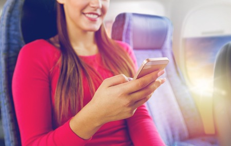close up of woman sitting in plane with smartphone
