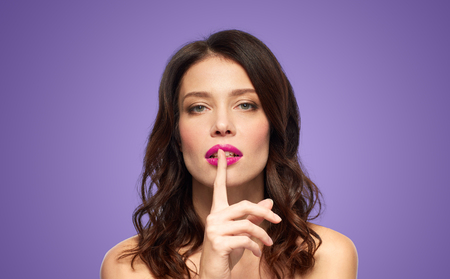 woman with pink lipstick holding finger on mouth
