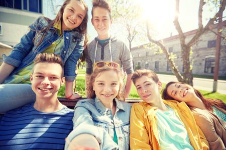 happy teenage students or friends taking selfie