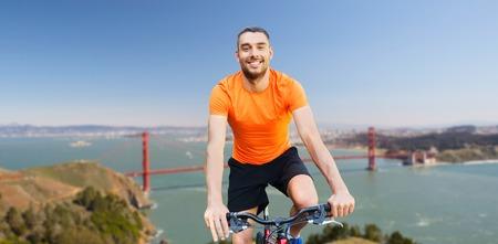 happy man riding bicycle over golden gate bridge Stock Photo