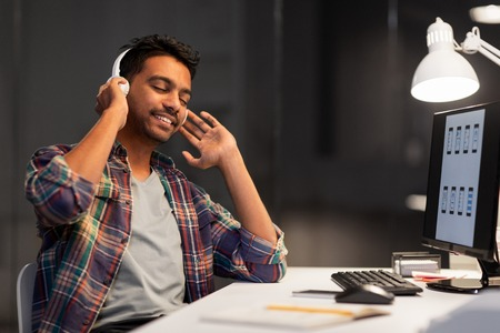 man with headphones listening to music at office