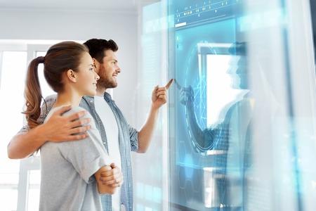 happy couple looking at futuristic virtual screen Stok Fotoğraf