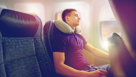 young man sleeping in plane with travel pillow