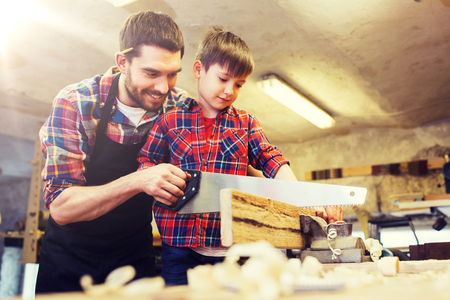father and son with saw working at workshop