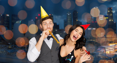 happy couple with party blowers having fun Stock Photo