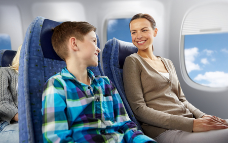 happy mother and son traveling by plane