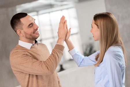 man and woman making high five at office