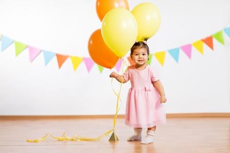 Neonata felice con palloncini sulla festa di compleanno Archivio Fotografico