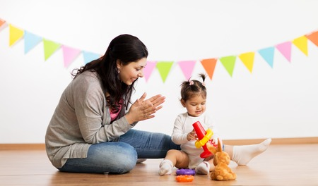 family, holidays and people concept - happy mother applauding for little daughter playing with ring pyramid baby toy on birthday party Stock Photo