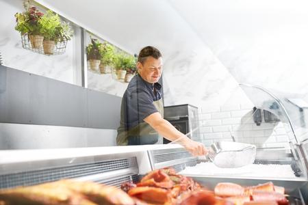 male seller adding ice to fridge at fish shop Stockfoto