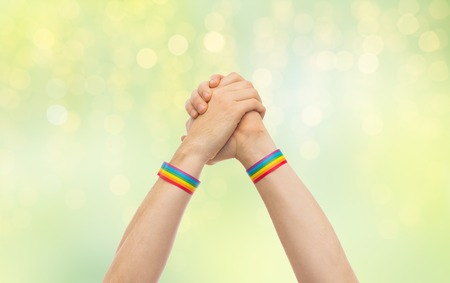 hands with gay pride wristbands in winning gesture