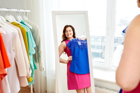 happy plus size woman in dress looking at mirror