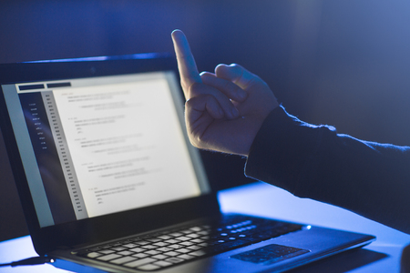 hacker showing middle finger to laptop