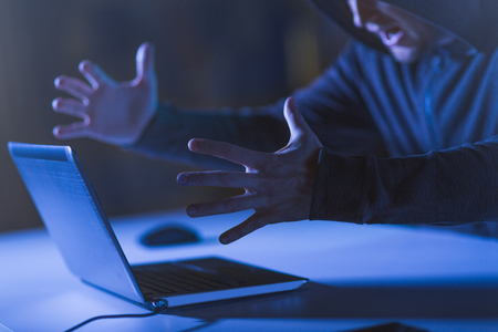 angry hacker with laptop shouting in dark room