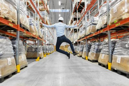 happy businessman in helmet jumping at warehouse Фото со стока - 100274832