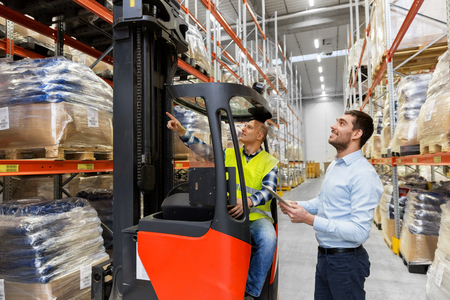 men with tablet pc and forklift at warehouse Stock Photo