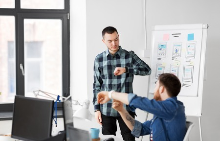 man showing smart watch to creative team at office