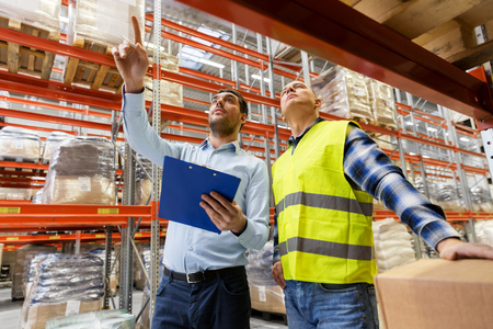 worker and businessman with clipboard at warehouse Stok Fotoğraf - 100275227
