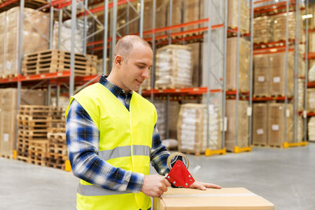 warehouse worker packing parcel with scotch tape