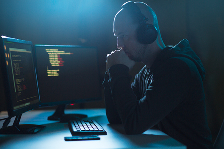 hacker with coding on laptop computer in dark room