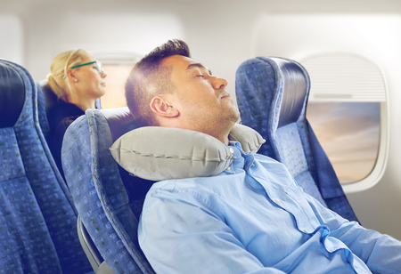 man sleeping in plane with cervical neck pillow