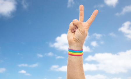 hand with gay pride rainbow wristband make peace