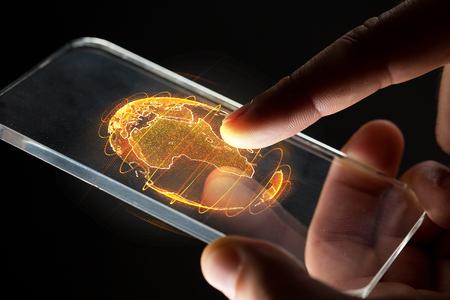 Manos con teléfono inteligente y holograma de tierra Foto de archivo - 100737085