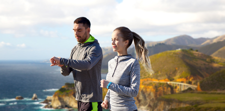 couple with fitness trackers running outdoors 版權商用圖片
