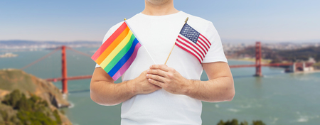 man with gay pride rainbow flag and american Stock Photo