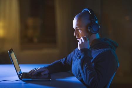hacker in headset typing on laptop in dark room