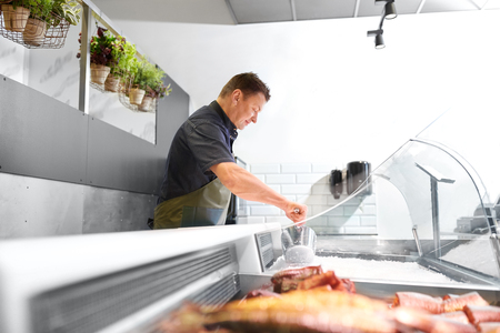 male seller adding ice to fridge at fish shop Stock Photo