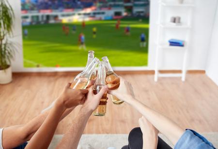 Freunde klirren Bier und schauen Fußballspiel Standard-Bild