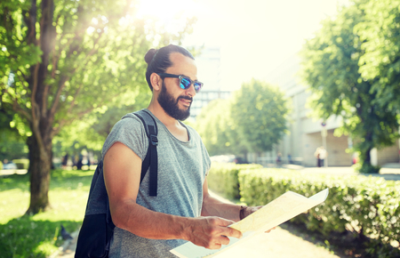 man traveling with backpack and map in city