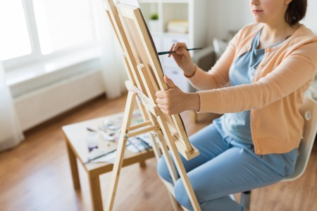 artist with easel and brush painting at art studio