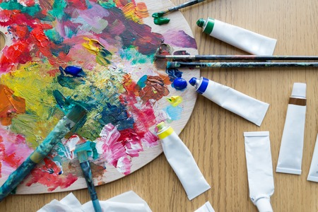 palette, brushes and paint tubes on table Фото со стока