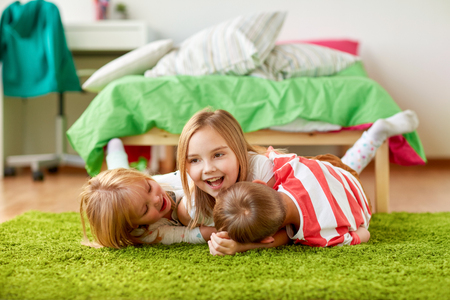 happy little kids lying on floor or carpet