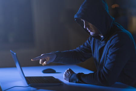 hacker pointing at laptop computer in dark room